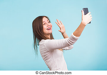 Young woman talking with friend through a video call on a smartphone. Beautiful girl having a video chat with man on mobile phone.