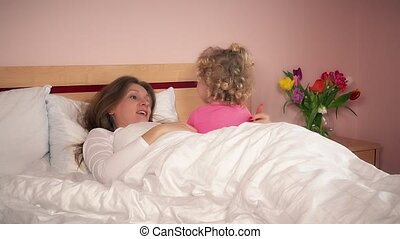 Young woman talking with her daughter girl in bedroom bed