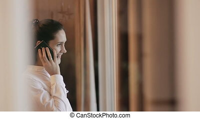 Young woman talks on the phone near the window