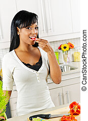 Young woman tasting vegetables in kitchen