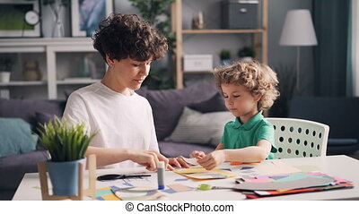 Young woman teaching her little son to make paper collage at table at home