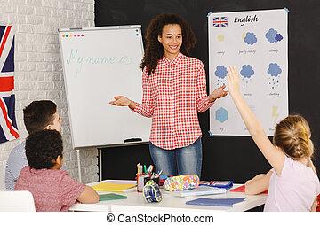 Young woman teaching kids - Young smiling woman teaching...