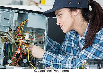 young woman technician repairing computer