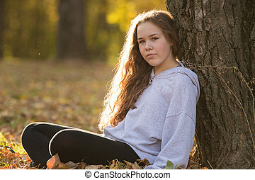 Young woman teenager standing by the tree in autumn park