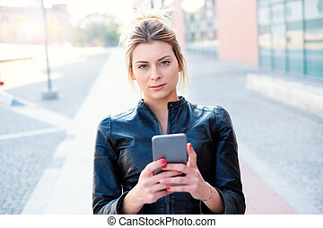 Young woman texting and using smart phone in the city