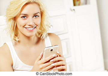 Young woman texting at home
