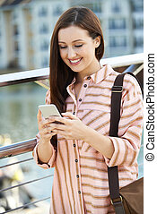 Young Woman Texting On Mobile Phone Walking To Work