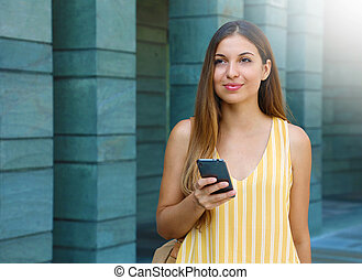 Young woman texting on smart phone outdoor.