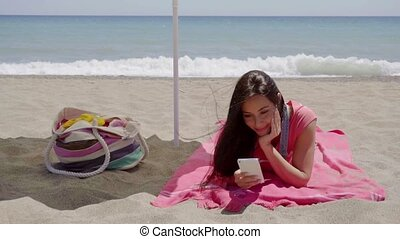 Young woman texting while relaxing on beach - Single happy...