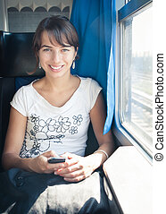 Young woman texting with her phone while traveling by train