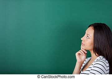 young woman thinking about something looking on blackboard