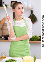 Young woman thinking about the menu while cooking in the kitchen. Housewife  holding a wooden spoon in her hand