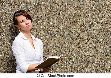 Young woman thinking and writing in her journal notebook