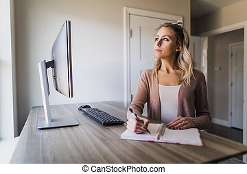 Young woman thinking and writing in her notebook in her home office