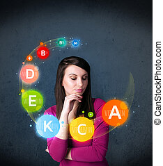 Thoughtful young woman with vitamin icons circulating around her head