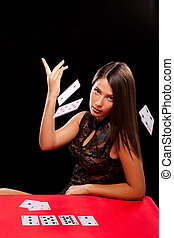 young woman throw playing cards in casino
