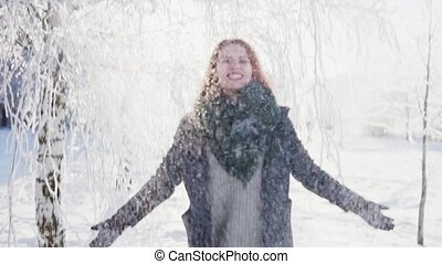 Young woman throw up a handful of snow and laughs, sunny...