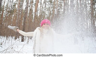 Young woman throws snow on park