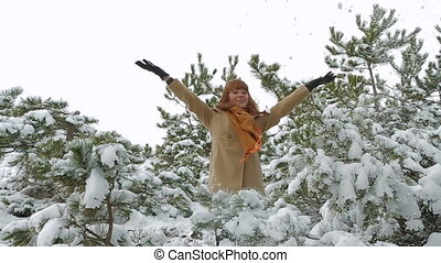 Young Woman Throws Up The Snow From The Trees