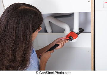 Young Woman Tightening Sink Pipe With Monkey Wrench