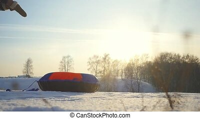 Young woman tobogganing on the mountains through the sun in slow motion in winter.