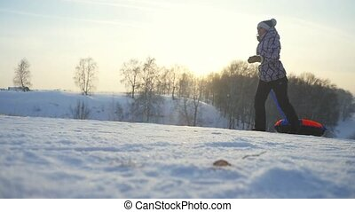 Young woman tobogganing running in the mountains through the sun in slow motion in winter have a good time. 1920x1080