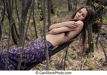 Young woman topless hiding her naked chests under her arms...