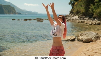 Young woman tosses pineapple standing on beach in summer day.