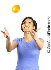 Young woman tossing an orange