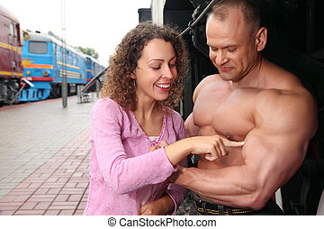 young woman  touches by finger  biceps of athlete