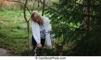 Young woman touching fir tree - Young blonde woman touching...