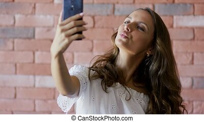 Young woman touching hair and taking selfie - Lovely young...