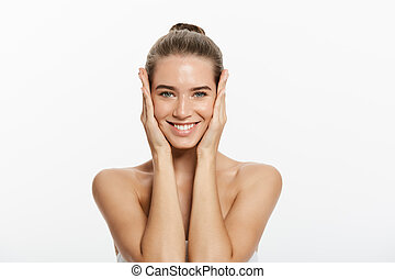 Young woman touching her face isolated on white background