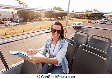 young woman touring the city on an open top bus