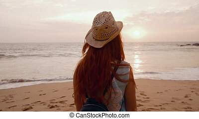 young woman tourist admiring the sunset on the ocean shore