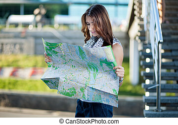 young woman tourist holding paper map outdoors