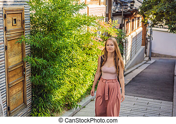Young woman tourist in Bukchon Hanok Village is one of the famous place for Korean traditional houses have been preserved. Travel to Korea Concept