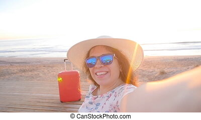 Young woman tourist making portrait photo on a beach