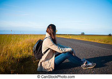 Young woman tourist sits on the road.