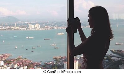 Young woman tourist standing at the window and photographed on a mobile phone view of a skyscraper height in Penang.