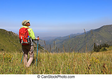 Young woman tourist stands in the middle of a meadow