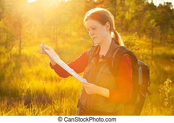 Young woman tourist with map portrait. Bright red sunset...