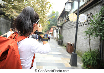 young woman tourist taking photo on street in chengdu,china
