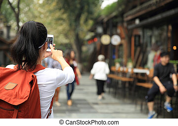young woman tourist taking photo with cellphone on street in chengdu,china
