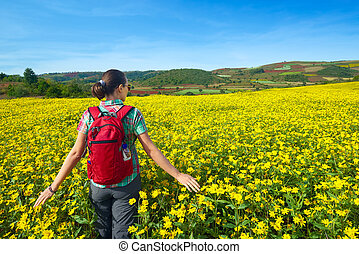 Young woman tourist walks on the background of colored fields.