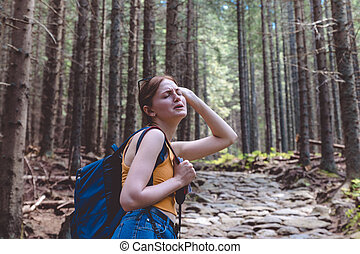 Young woman tourist with a backpack in the forest, tired of walking