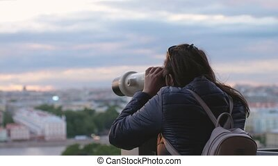 Young woman tourist with backpack looking at city through coin-operated binoculars during sunset time in slow motion.