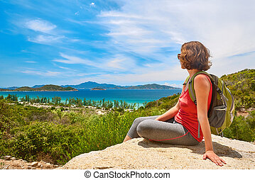 Young woman tourist with backpack sit on a rock on clear sky background, looking at beautiful landscape
