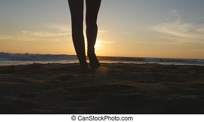 Young woman tourist with backpack walking on beach to the ocean at sunset and raised hands. Girl hiker going on sandy shore to the sea and enjoying freedom during summer vacation. Rear back view