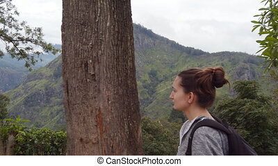 Young woman tourist with backpack walking at trail in mountains with beautiful nature landscape at background. Female hiker going along tropical mount road. Healthy active lifestyle. Travel concept